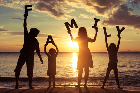 """Gelukkige familie die zich op het strand bij de zonsondergang tijd. Ze houden de letters die het woord """"familie"""". Concept van vriendelijke familie. Stockfoto"""