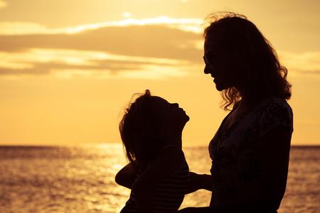 silueta niño: Madre e hijo jugando en la playa de la puesta del sol. Concepto de la familia.