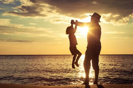 Padre e hijo jugando en la playa de la puesta del sol. Concepto de la familia.