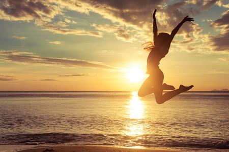 brincando: Muchacha adolescente feliz saltando en la playa a la hora del atardecer Foto de archivo