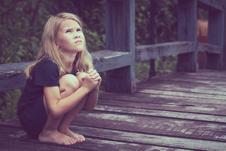 lost: Portrait of sad blond little girl sitting on the bridge at the day time