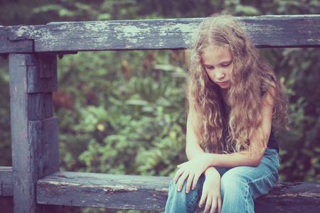 niños tristes: Retrato de la muchacha triste adolescente rubia sentada en el puente en el tiempo del día