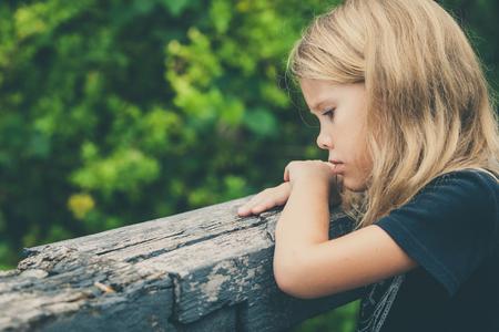 petite fille triste: Portrait de triste blonde petite fille assise sur le pont au moment de la journ�e