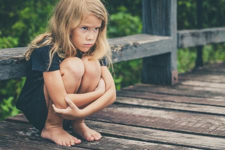 ansiedad: Retrato de niña triste rubia sentada en el puente en el tiempo del día