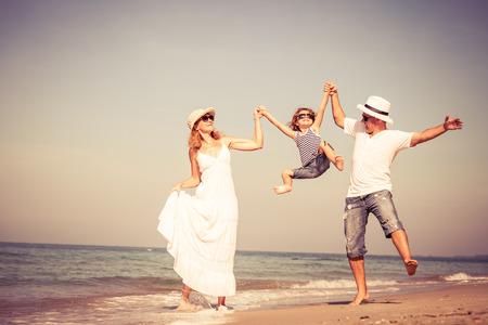 家人: 幸福的家庭走在沙灘上,在一天的時間。概念的友好家庭。