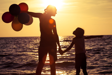 sun beach: Mother and daughter playing on the beach at the sunset time. Concept of friendly family.