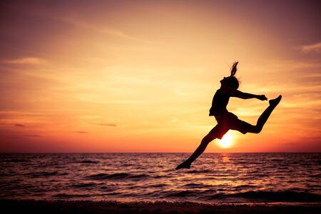 personas saltando: Muchacha adolescente feliz saltando en la playa a la hora del atardecer Foto de archivo