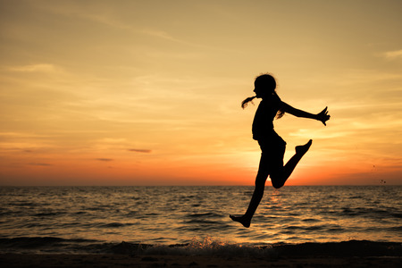 teen silhouette: Happy teen girl  jumping on the beach at the sunset time