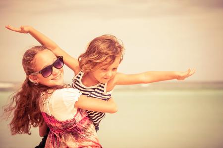 Schwester und Bruder spielen am Strand an der Tageszeit. Konzept Bruder und Schwester zusammen für immer