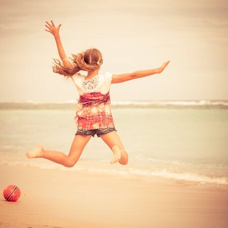 family fun: Happy teen girl  jumping on the beach at the day time