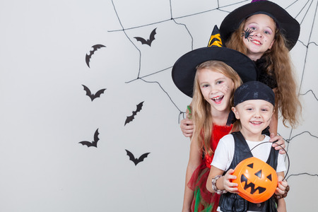 tricks: Happy brother and two sisters on Halloween party
