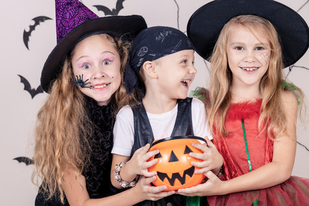 costumes: Happy brother and two sisters on Halloween party