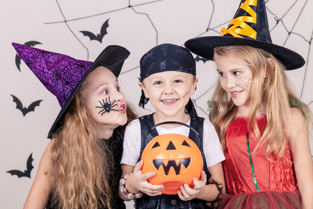horror: Happy brother and two sisters on Halloween party