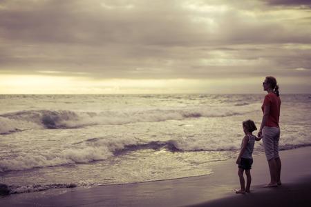 mama e hijo: Madre e hijo jugando en la playa en el día. Concepto de la familia.