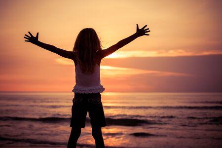 silueta niño: Niña feliz de pie en la playa de la hora del atardecer Foto de archivo