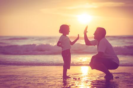 amistad: Padre e hijo jugando en la playa de la puesta del sol. Concepto de la familia.