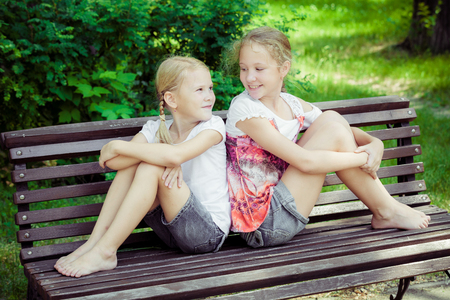 cute little girl: Two happy children  playing near the tree at the day time. Concept Two Sisters Together Forever Stock Photo