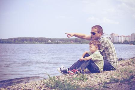 pareja en casa: Padre y niños jugando en el parque en el banco en el momento en día. Concepto de la familia. Foto de archivo