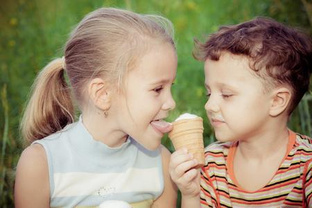 niña comiendo: Dos niños felices jugando cerca del árbol en el tiempo del día. Concepto Hermano y hermana Juntos para siempre