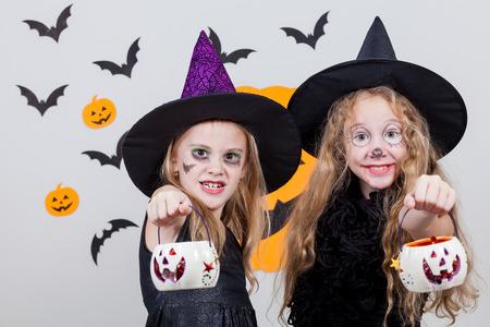 treats: Dos hermanas felices en la fiesta de Halloween