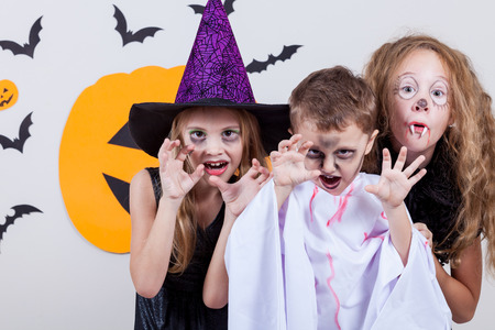 kids party: Happy brother and two sisters on Halloween party
