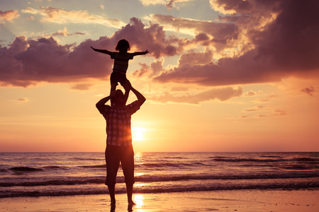 família: Pai e filho brincando na praia no momento do por do sol. Conceito de fam Banco de Imagens