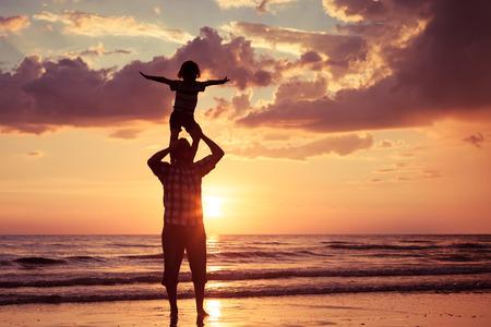 family: Vader en zoon spelen op het strand bij de zonsondergang tijd. Concept van de vriendelijke familie.