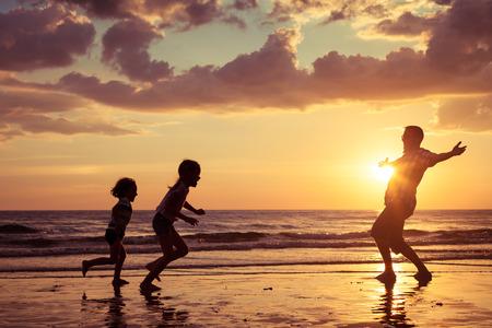 Padre y niños que juegan en la playa de la puesta del sol. Concepto de la familia.