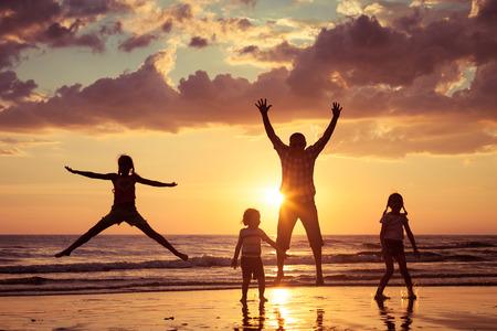 boy jumping: Padre y ni�os que juegan en la playa de la puesta del sol. Concepto de la familia.