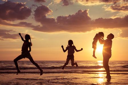 Vader en kinderen spelen op het strand bij de zonsondergang tijd. Concept van de vriendelijke familie.