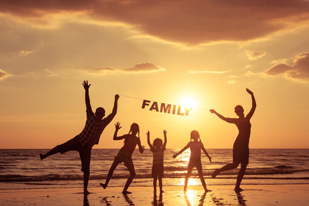 Happy family standing on the beach at the sunset time. Parents hold in the hands  inscription Family. Concept of happy family.