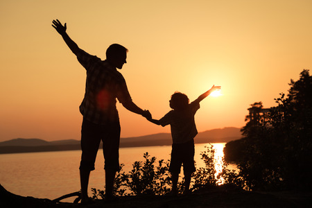 padre e hijo: padre e hijo jugando en la costa del lago en las montañas de la puesta del sol en el momento
