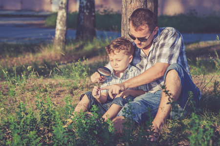 discovery: Father and son playing in the park at the day time. Concept of friendly family. Stock Photo