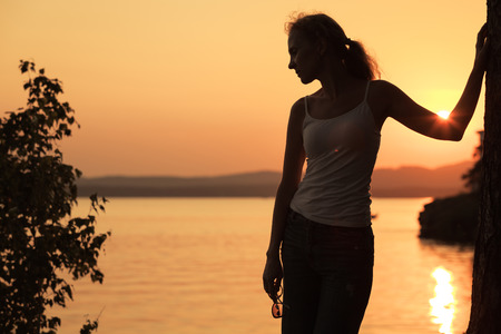 stress free: Silhouette of woman who standing on the coast of lake at the sunset time.