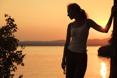 ansiedad: Silueta de la mujer que se coloca en la costa del lago en la puesta del sol. Foto de archivo