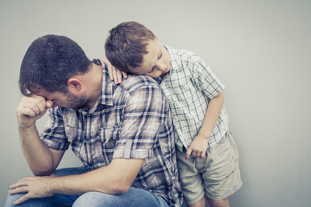 children sad: sad son hugging his dad near wall of house at the day time