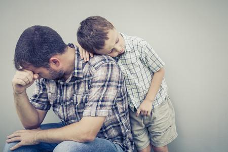 niños tristes: triste hijo abrazando a su padre cerca de la pared de la casa en el momento día Foto de archivo