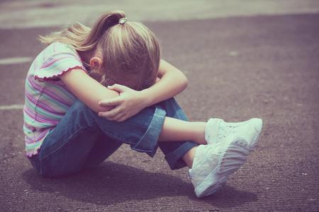 depresión: Retrato de la niña triste que se sienta en el camino en el día. Foto de archivo