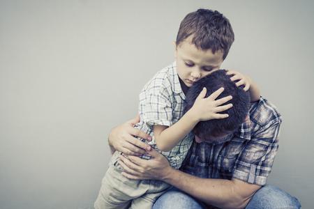 problemas familiares: triste hijo abrazando a su padre cerca de la pared de la casa en el momento día Foto de archivo