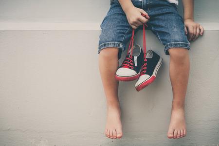 juventud: Niño sentado cerca de la casa y mantener las zapatillas de deporte de la juventud en sus manos en el tiempo del día.