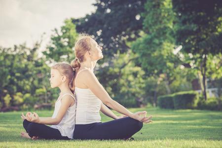 母と娘の一日の時間で公園の芝生の上はヨガの練習を行う 写真素材