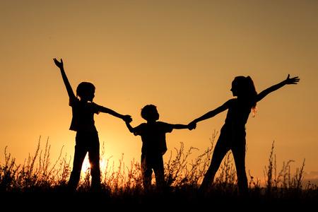 niños jugando: Felices los niños jugando en el parque a la hora del atardecer. Foto de archivo