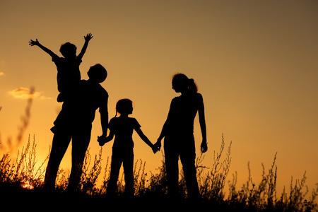 Gelukkige familie die zich in het park bij de zonsondergang tijd. Concept van de vriendelijke familie.