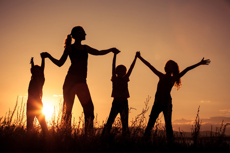field sunset: Happy family standing near the lake at the day time.  Concept of friendly family.