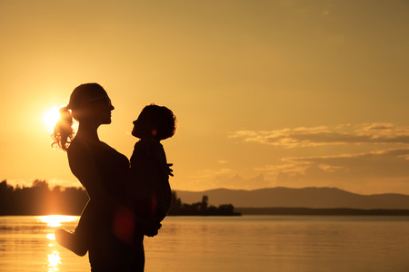 Mother and son playing on the coast of lake in the mountains of at the sunset time.  Concept of friendly family.
