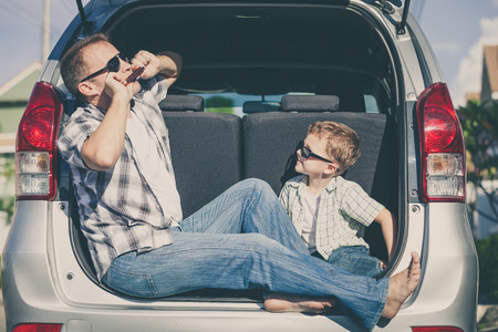 uomo felice: Happy father and son getting ready for road trip on a sunny day.  Concept of friendly family.