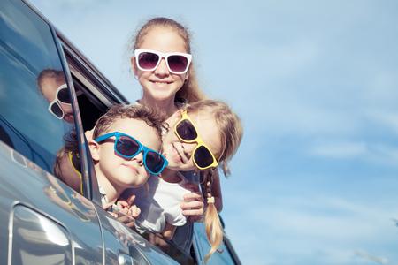 Szczęśliwe dzieci przygotowują się do podróży drogi w słoneczny dzień. Koncepcja przyjazny rodzinie. Zdjęcie Seryjne