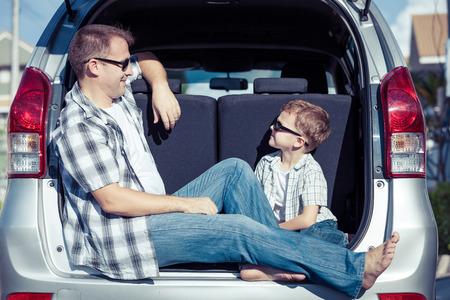 Gelukkig vader en zoon zich klaar voor road trip op een zonnige dag. Concept van vriendelijke familie. Stockfoto