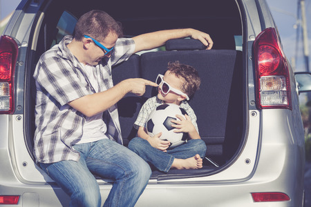 cool kids: Happy father and son getting ready for road trip on a sunny day.  Concept of friendly family.