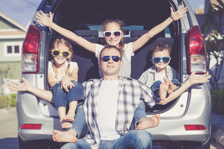 Happy family getting ready for road trip on a sunny day.  Concept of friendly family. Stock Photo